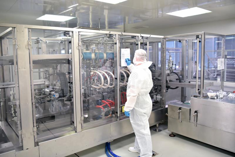 worker in sterile protective clothing in a clean room of a pharamzie company operates the technical plant for the production of d stock images