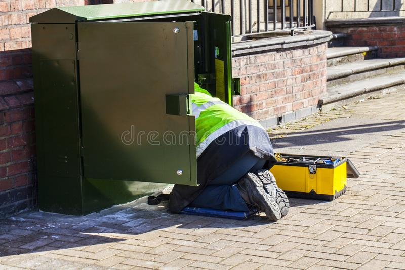 Worker on the street working in electricity box. Security on the work conceptual image. Man on the knees working on the royalty free stock photo