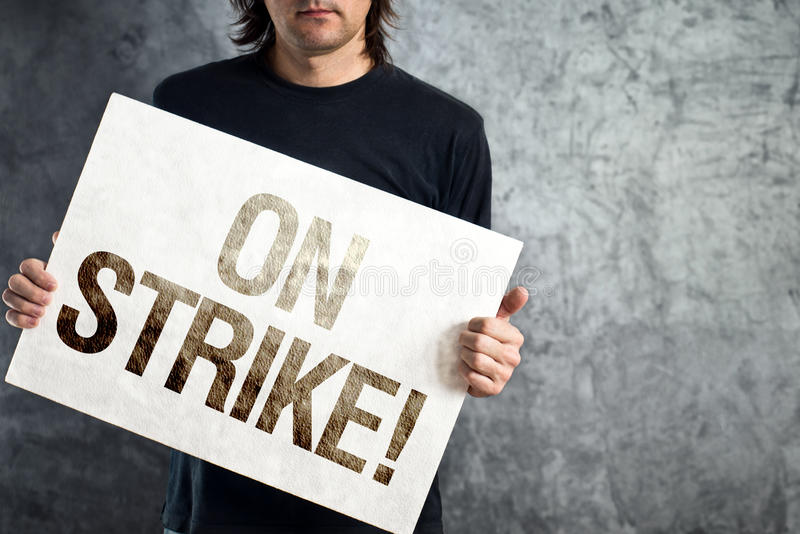 Worker on strike, man holding poster with printed protest message royalty free stock photography