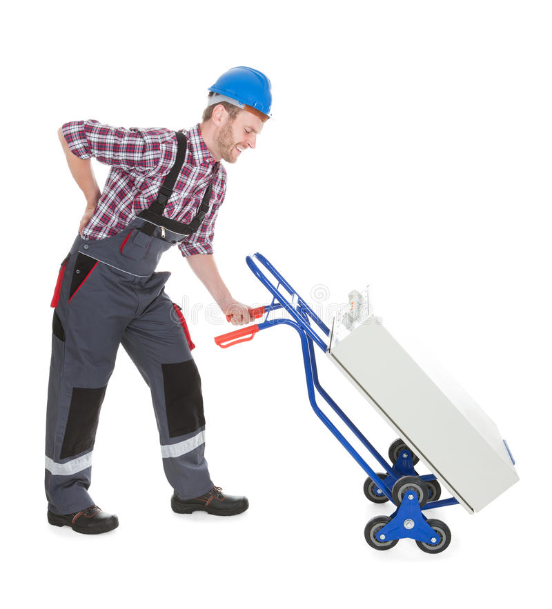 Worker Suffering From Backache While Pushing Machinery royalty free stock photo