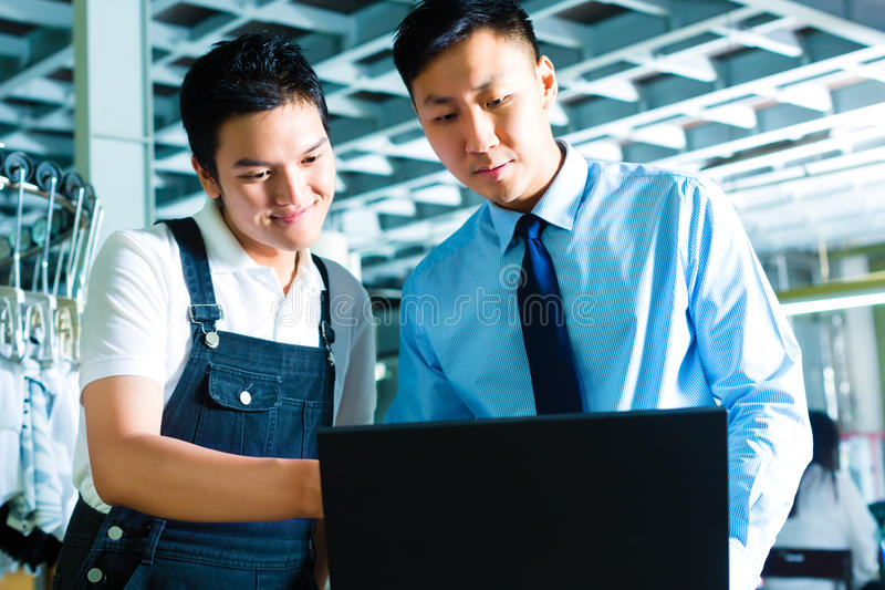 Worker and supervisor with laptop in a factory. Chinese Worker or production manager and owner, ceo or controller, look on a laptop in a textile factory royalty free stock image