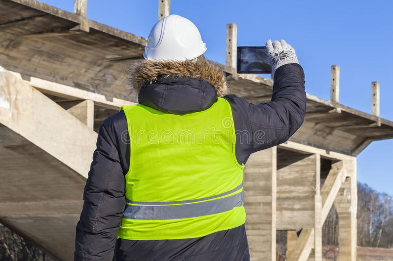 Worker take pictures on tablet near the unfinished bridge stock photography