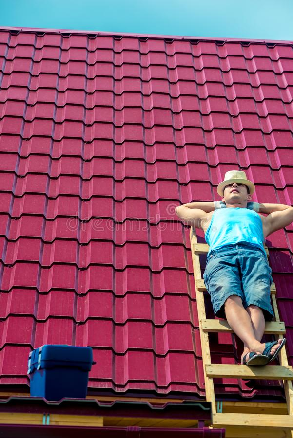 A worker takes a sun bath on the roof of the house during stock photo
