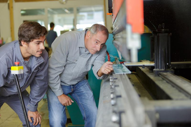 Worker team in factory discussing in front machine. Worker team in factory discussing in front of machine stock image