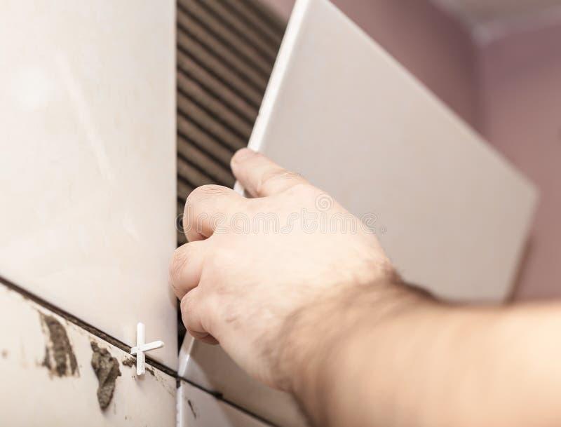 Worker tiler puts ceramic tiles stock images