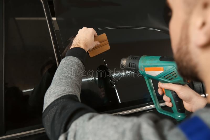 Worker tinting car window in shop. Closeup stock photo