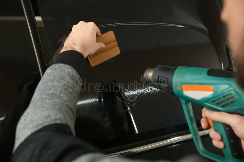 Worker tinting car window in shop. Closeup stock images