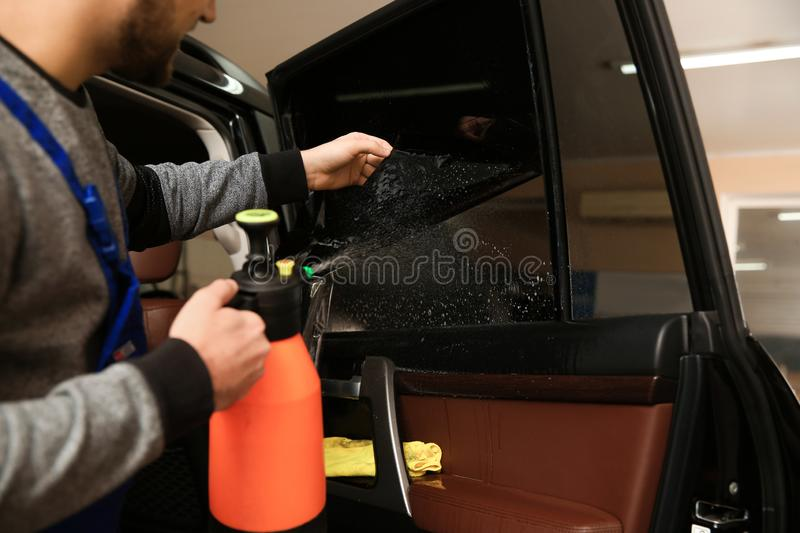 Worker tinting car window in shop. Closeup royalty free stock images