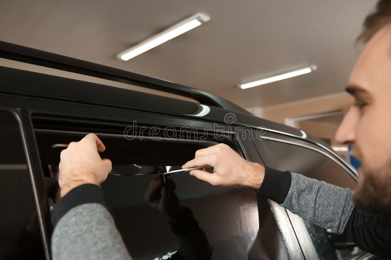 Worker tinting car window in shop. Closeup royalty free stock image