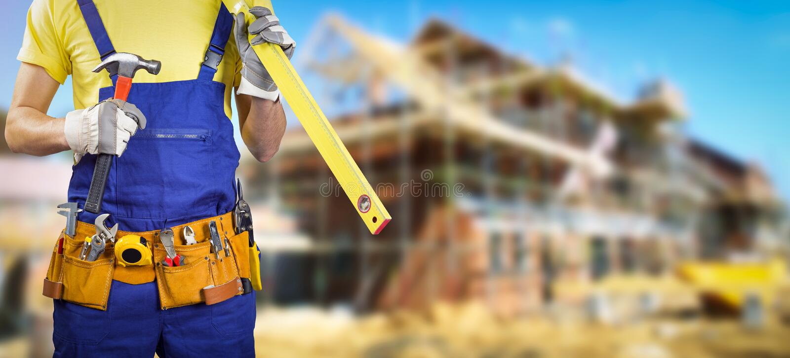 Worker with tool belt in house construction site royalty free stock images