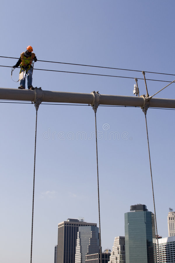Worker on top of Brooklyn Bridge in New York City royalty free stock image