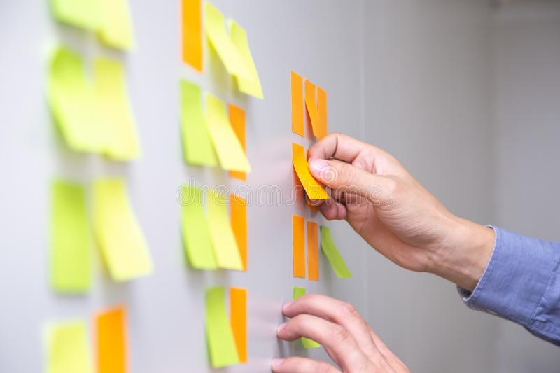 IT worker tracking his tasks on kanban board. Using task control of agile development methodology. Man attaching sticky note to scrum task board in the office royalty free stock images