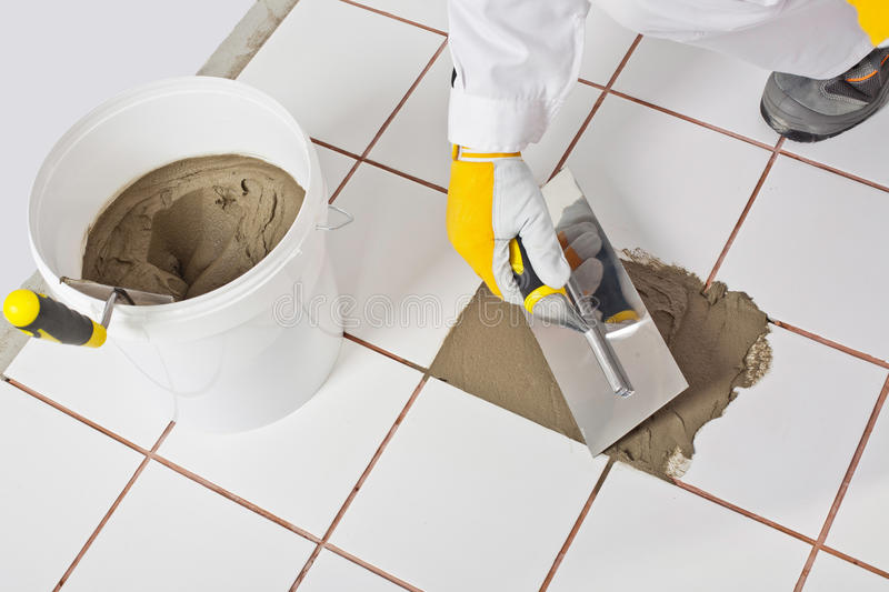 Worker trowel repairs tiles ti. Worker with trowel repairs old white tiles with tile adhesive stock images