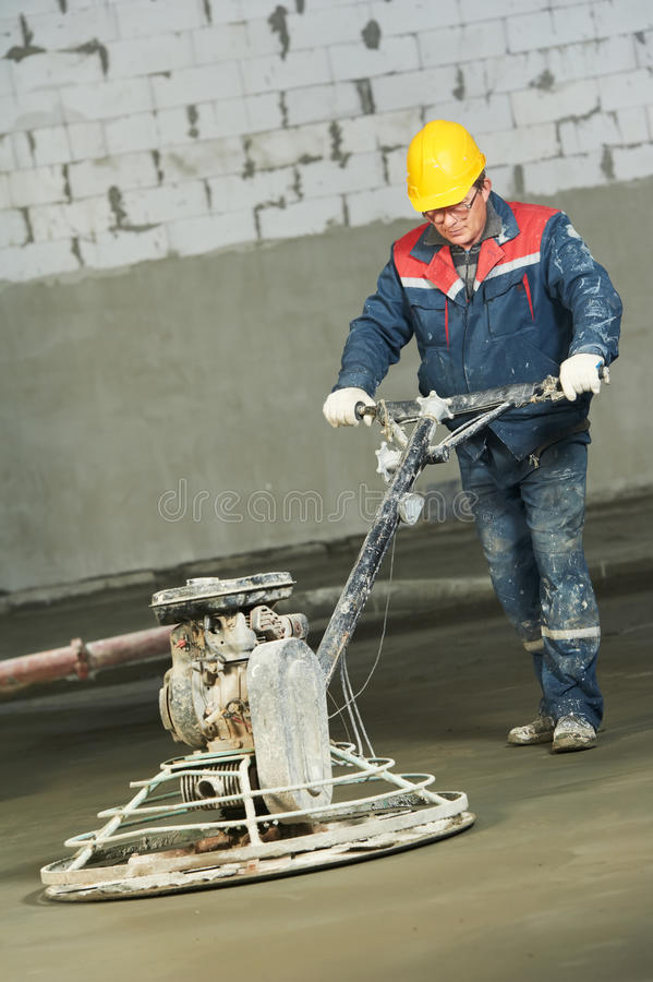 Worker trowelling and finishing of concrete stock photography