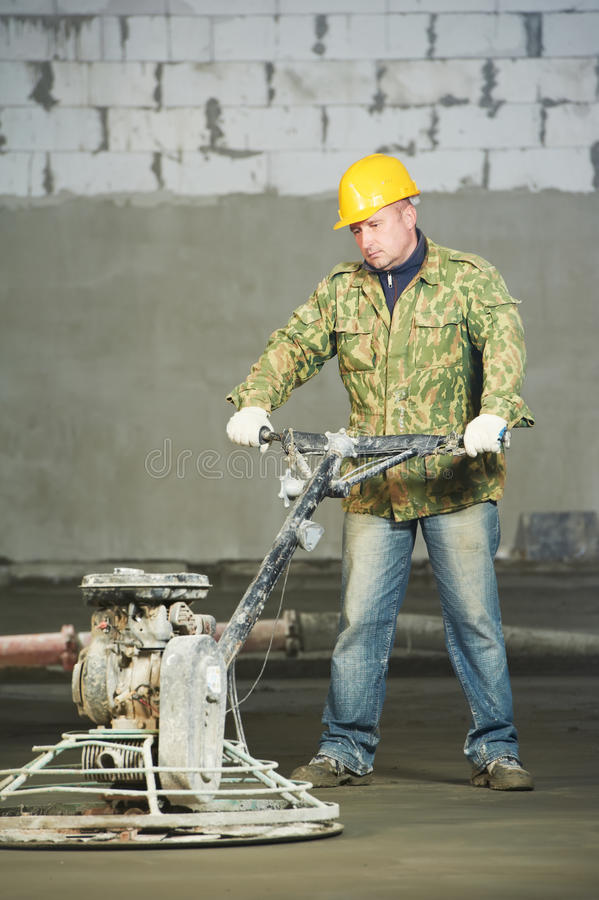 Worker trowelling and finishing of concrete. By special construction equipmant stock photo