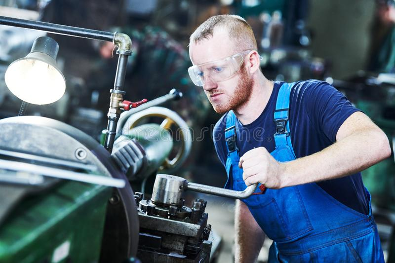 Worker turner operating lathe machine at industrial manufacturing factory stock images