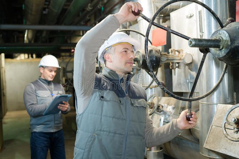 Worker turning industrial knob royalty free stock photography