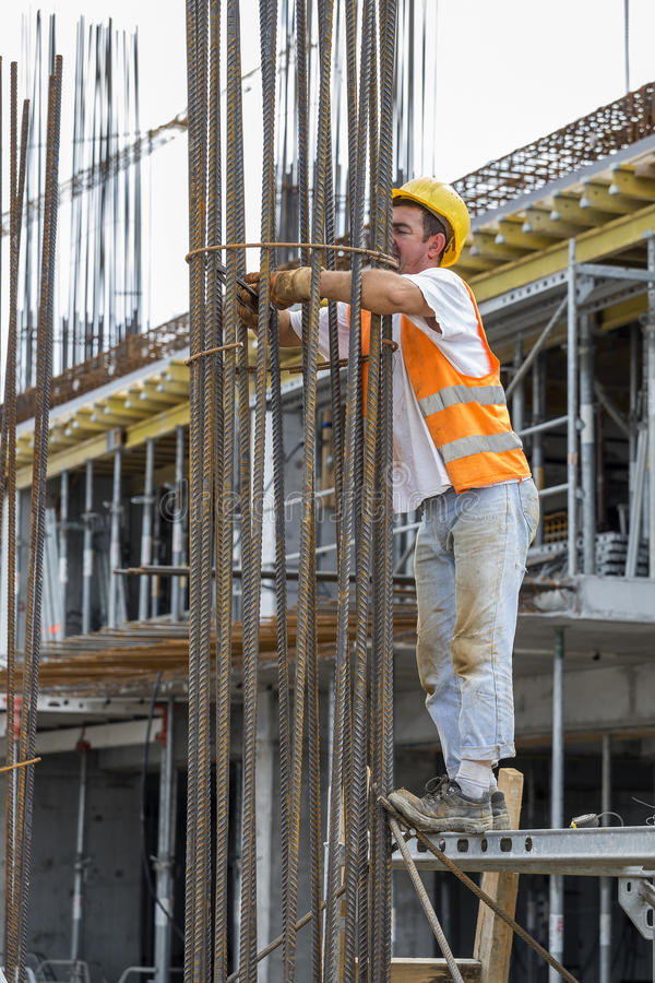 Worker tying reinforcing steel bars with plier and wire. BELGRADE, SERBIA - SEPTEMBER 08, 2016: Worker tying reinforcing steel bars with plier and wire on stock image