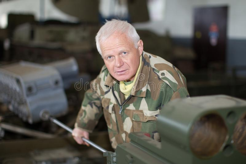 Worker in uniform measures wear of gun barrel stock photo