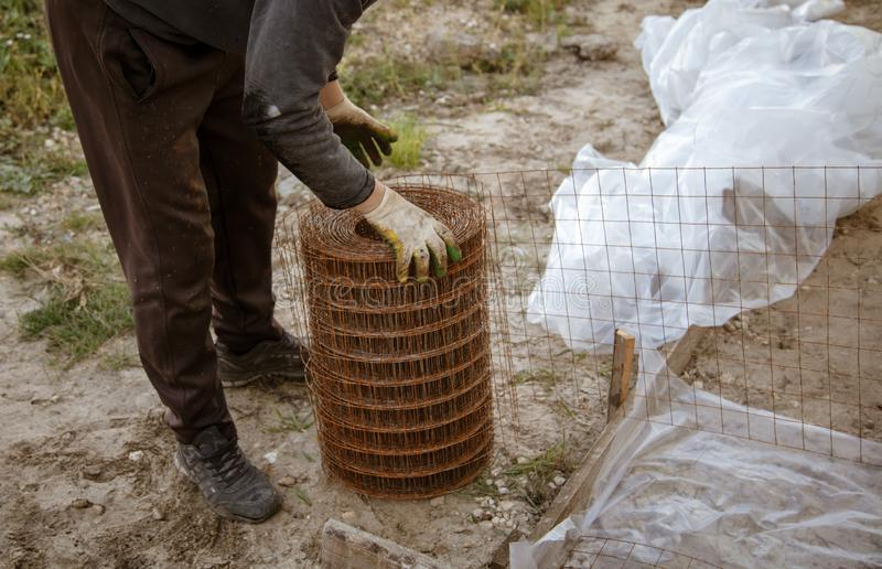 Worker unwinds a metal mesh for pouring concrete.  royalty free stock images