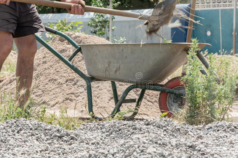 Worker use the shovel and fill the wheelbarrow with construction waste stock photo