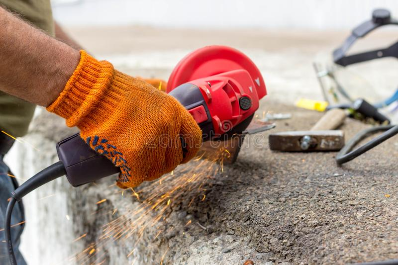 The worker uses an angle drive grinder to work with a metal corner. Angle drive grinder in action stock image