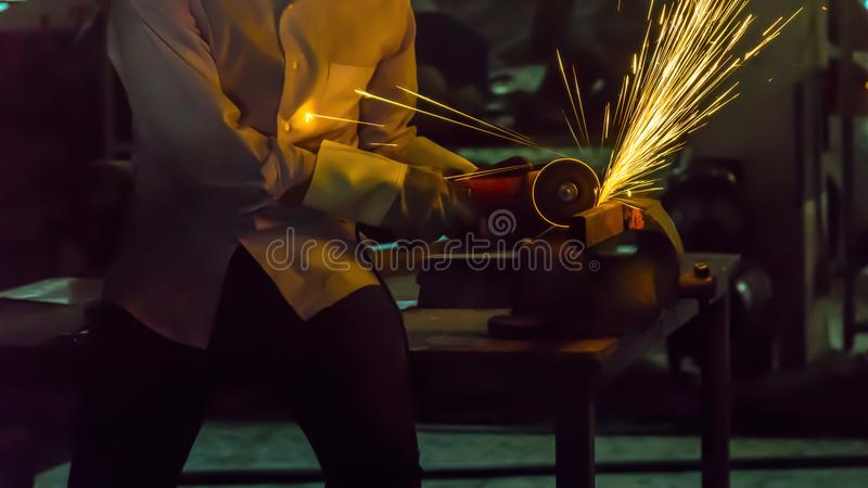the worker uses cutting machine to cut metal, focus on flash light line of sharp spark,in low Light stock image