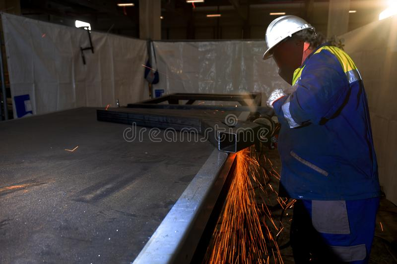 Worker using angle grinder on construction site stock image