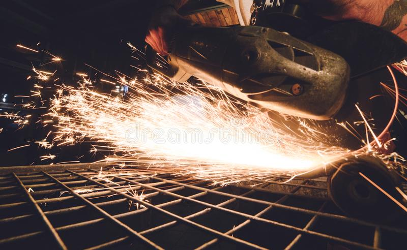 Worker Using Angle Grinder in Factory and throwing sparks. royalty free stock image
