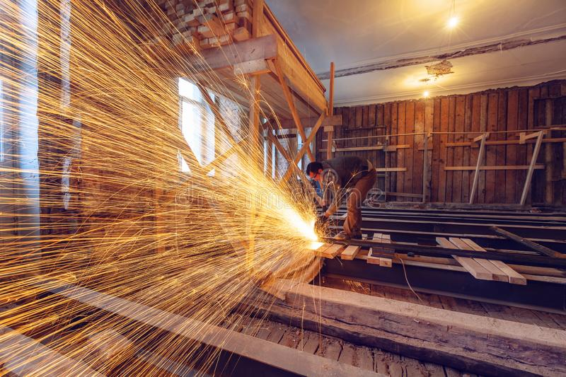 Worker is using angle grinder with fountain of sparks in apartment that is under construction, remodeling, renovation stock photography