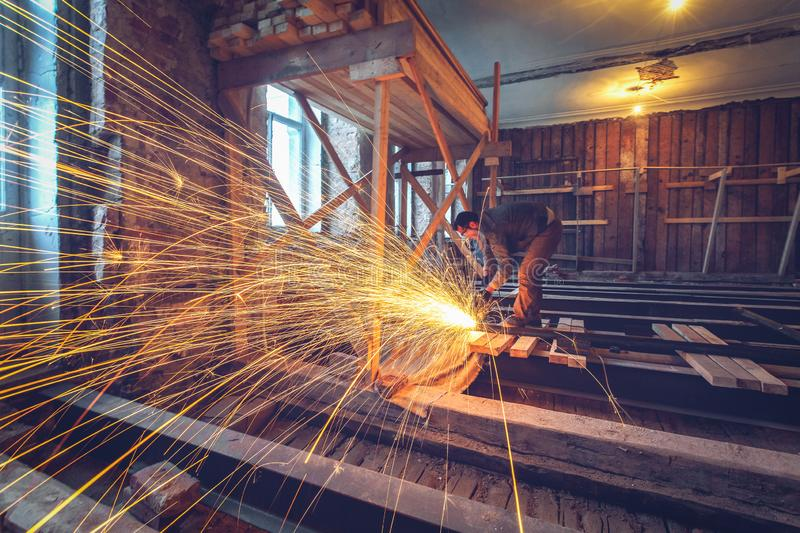 Worker is using angle grinder with fountain of sparks in apartment that is under construction, remodeling, renovation. Overhaul, extension, restoration and stock photography