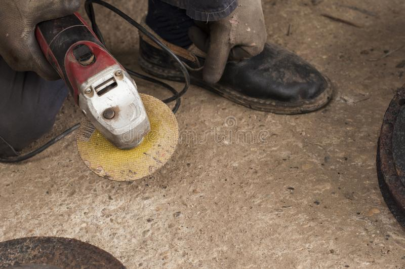 Worker using angle grinder in workshop.Car disk processing royalty free stock photo