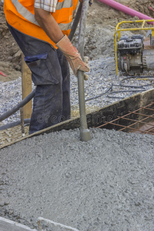 Worker using concrete vibrator 2. Worker using concrete vibrator for maximum strength and consistency in concrete. Selective focus and shallow dof royalty free stock photography