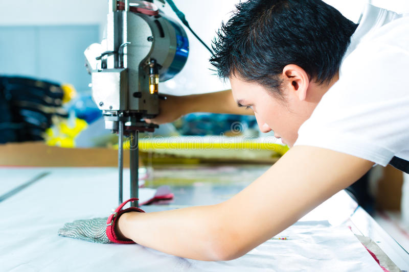 Worker using a machine in chinese factory stock photo