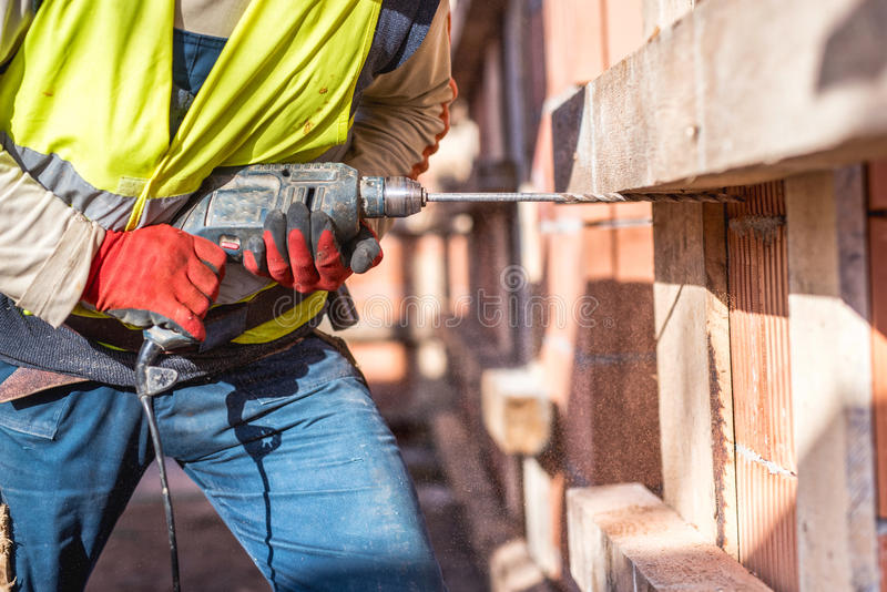 Worker using a drilling power tool on construction site. And creating holes in bricks royalty free stock image