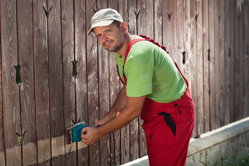 Worker using electric sander to remove old paint stock image