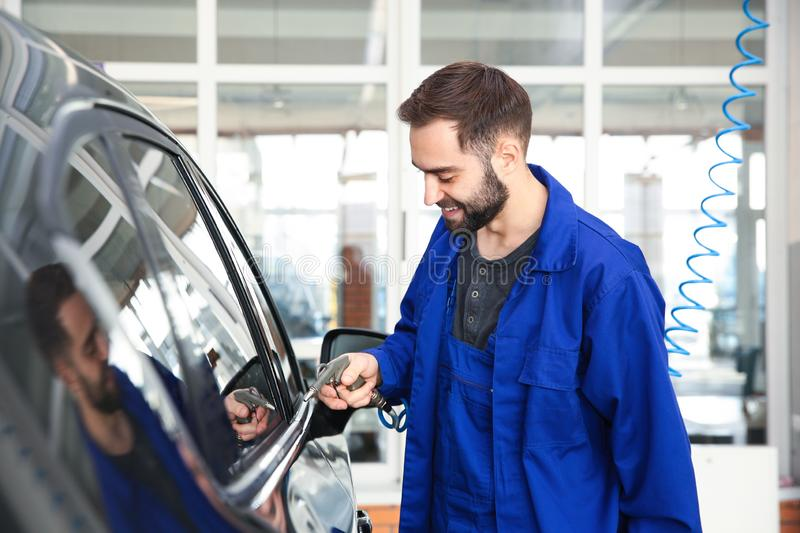 Worker using gun for auto cleaning. At car wash royalty free stock photography