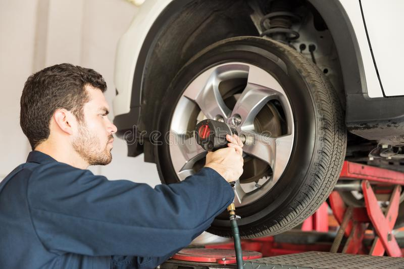 Worker Using Impact Wrench On Change Tire. Confident worker using impact wrench on change tire in repair shop stock photos