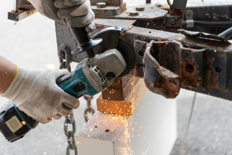 Worker using a metal grinder machine to cut off a piece of metal stock photography
