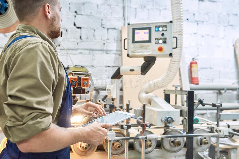 Worker Using Modern Machine at Factory stock images