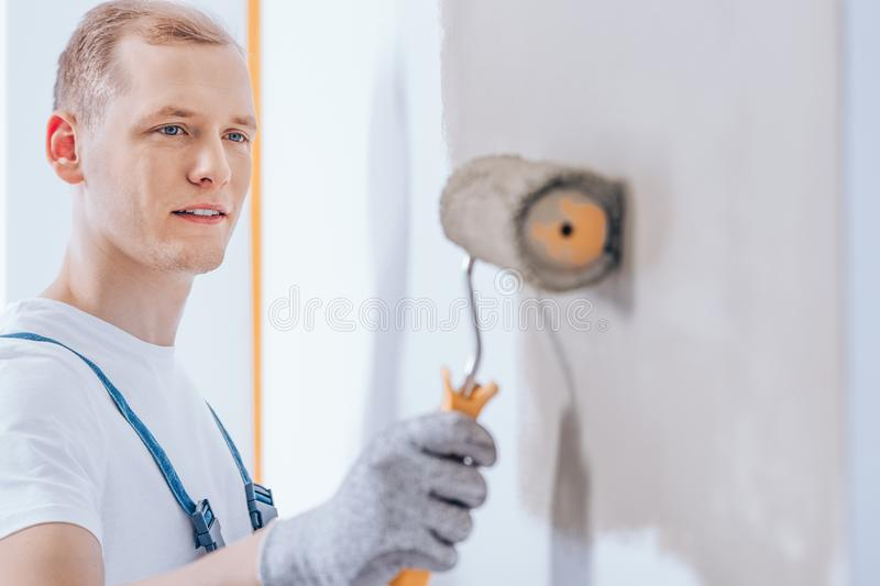 Worker using paint roller stock images