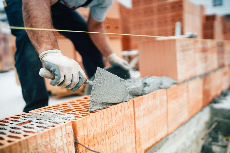 Worker using pan knife for building brick walls with cement and mortar. Professional worker using pan knife for building brick walls with cement and mortar royalty free stock image