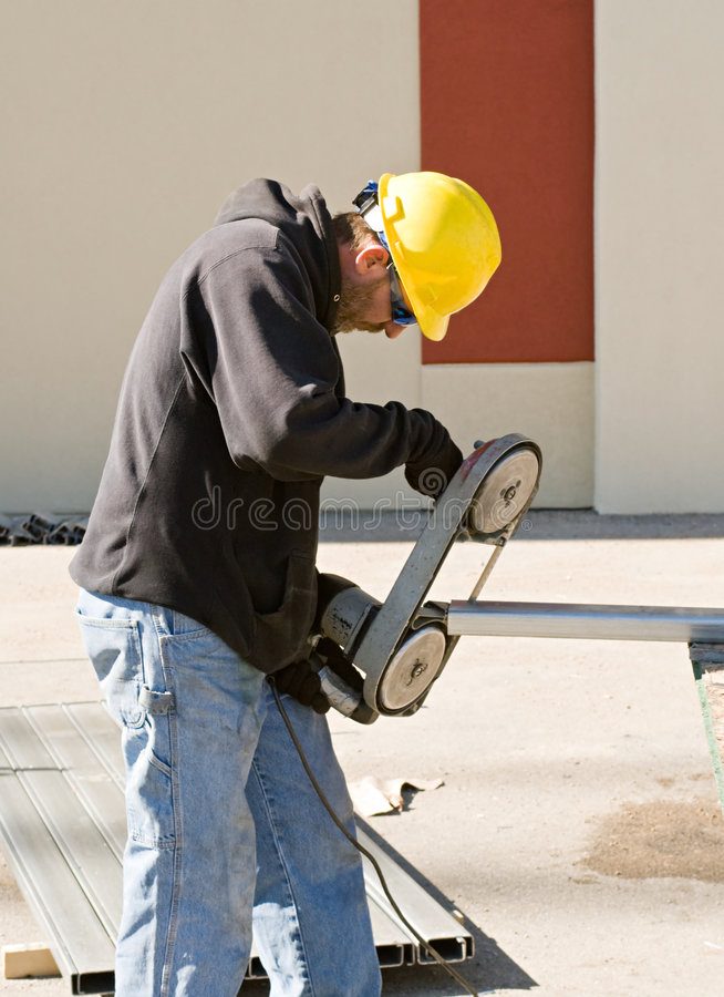 Worker Using Porta-Band Saw. Construction worker using porta-band saw to hand-cut metal stud royalty free stock photography