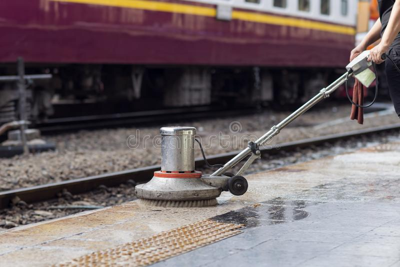 Worker using scrubber machine for cleaning and polishing floor. Cleaning maintenance train at railway station stock image