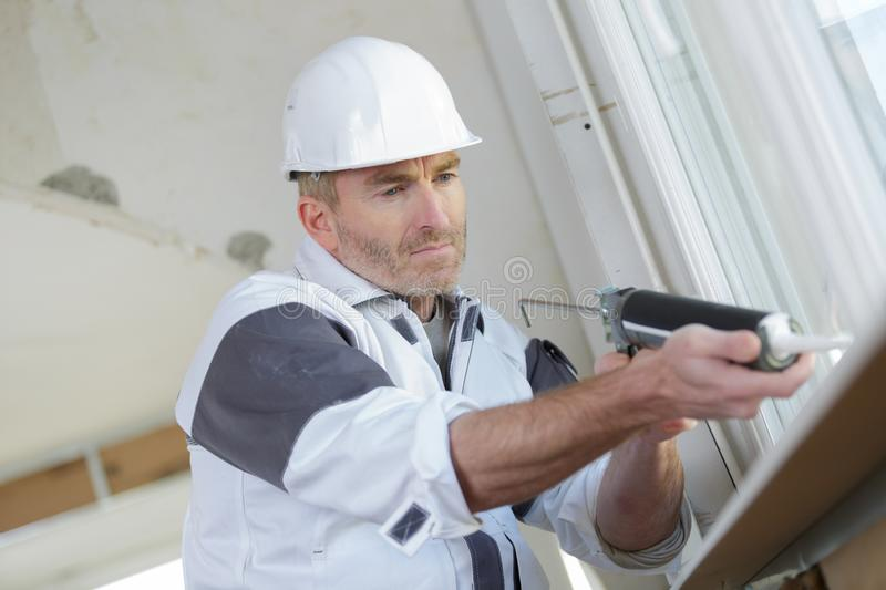 Worker using silicone tube for repairing window royalty free stock photos