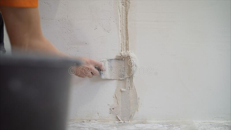 Worker using the trowel for plastering the concrete wall at the construction site. Making the smoothness and flat the surface of royalty free stock photo