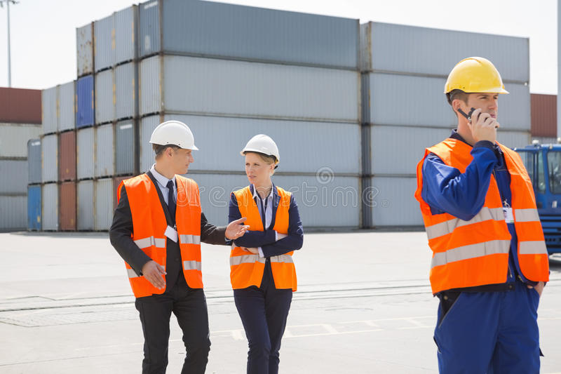 Worker using walkie-talkie while colleagues discussing in shipping yard royalty free stock images