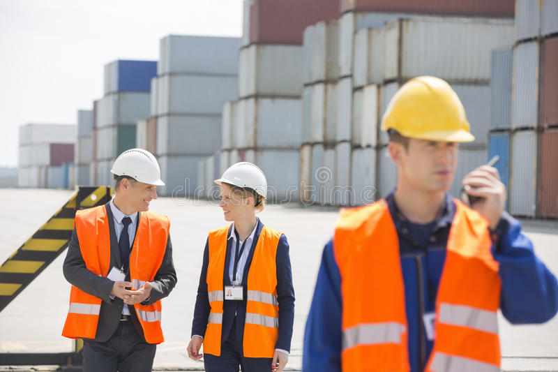 Worker using walkie-talkie while colleagues discussing in shipping yard royalty free stock photo