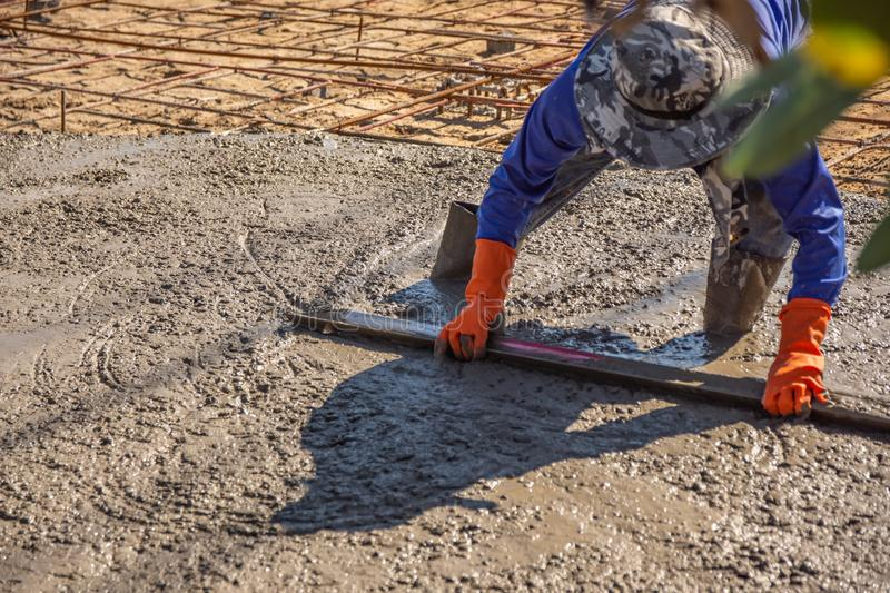 Worker using a wooden spatula for cement after Pouring ready-mixed concrete. On steel reinforcement to make the road by mixing mobile the concrete mixer royalty free stock photo