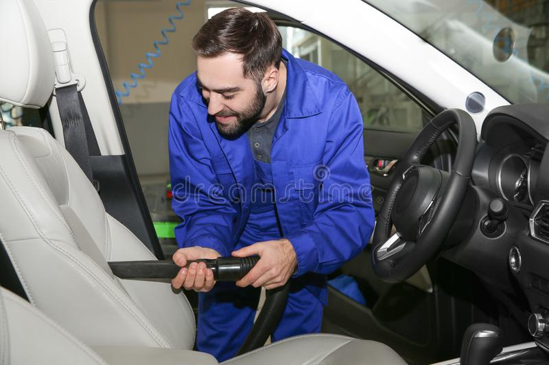 Worker vacuuming automobile seat. Car wash service. Worker vacuuming automobile seat, view from inside. Car wash service stock photo
